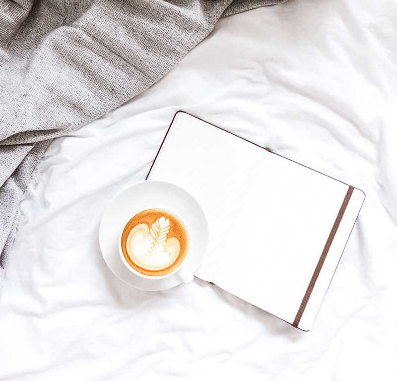coffee and journal in a bed