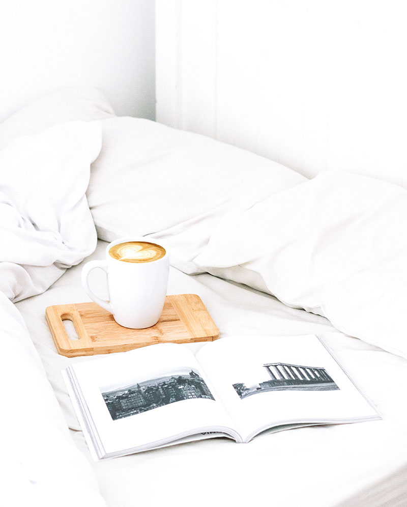cup of coffee with a book on a bed