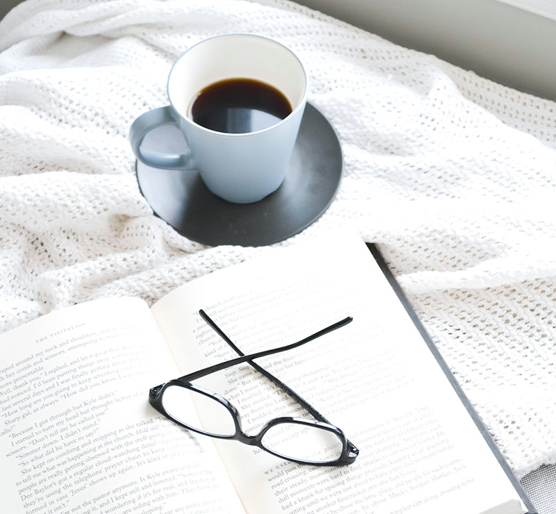 coffee cup with book on a blanket