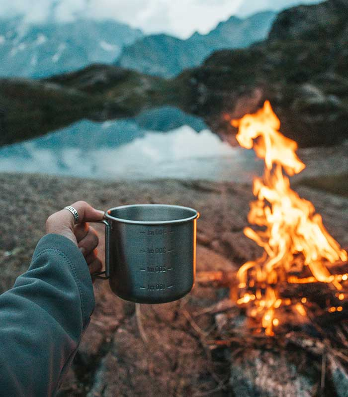 camping with a mug and a bonfire